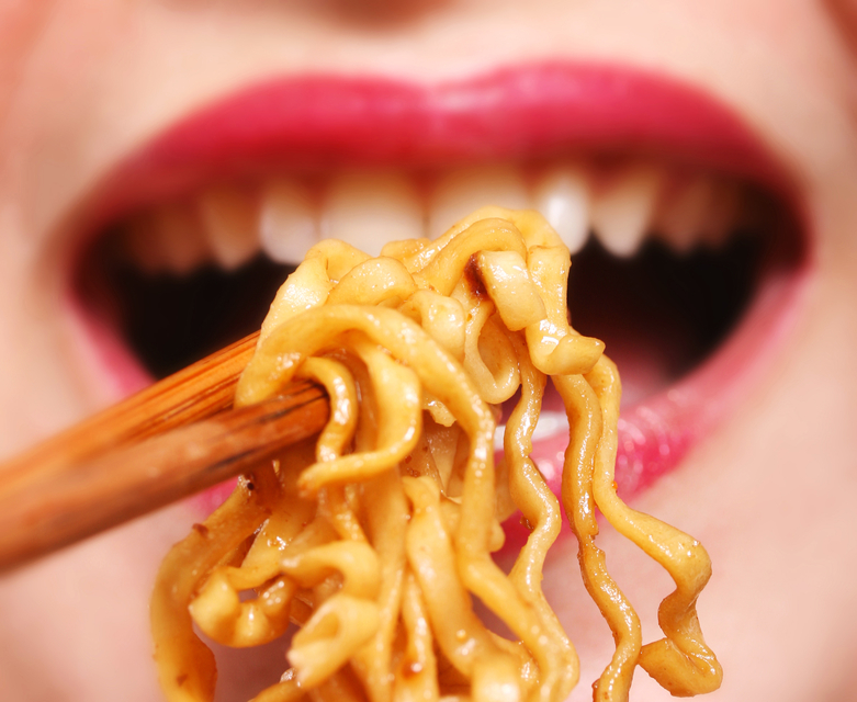 Young chinese woman eating noodles