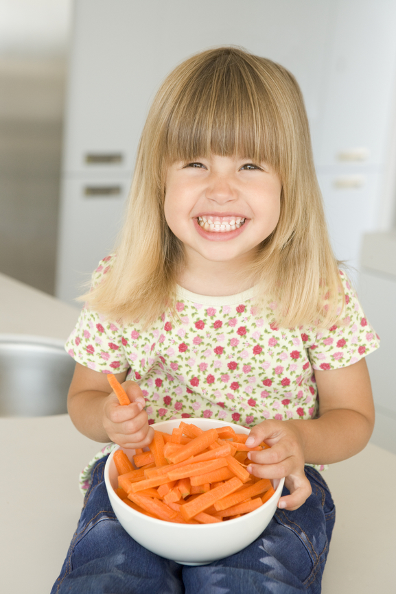 Young girl in kitchen eating carrot sticks smiling