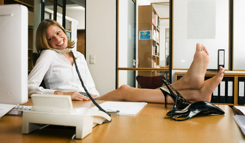 Young businesswoman with her feet up on her desk