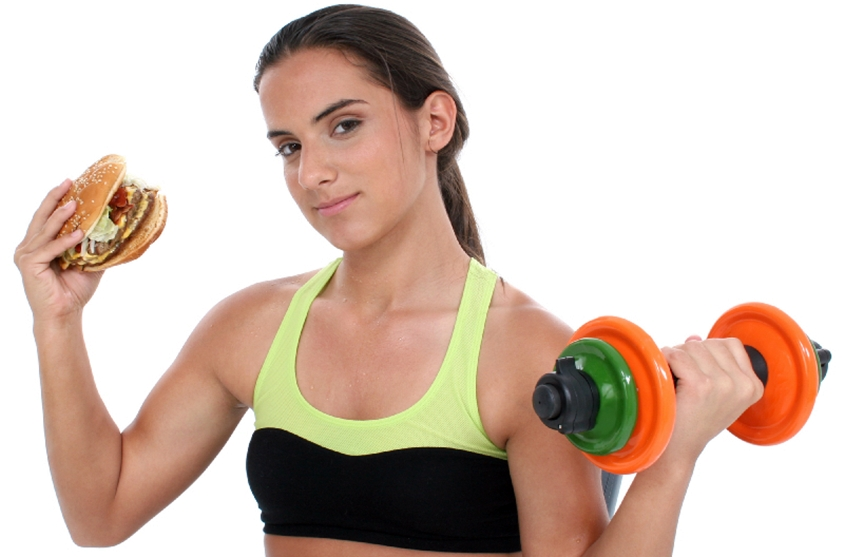 Beautiful Teen Girl Holding Colorful Weights And A Giant Cheeseb