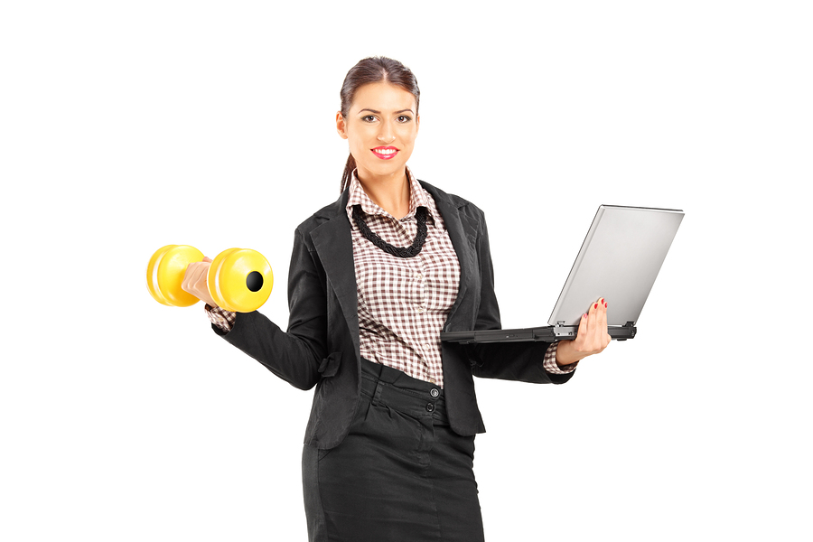 Busy smiling businesswoman holding a laptop and lifting a dumbbe