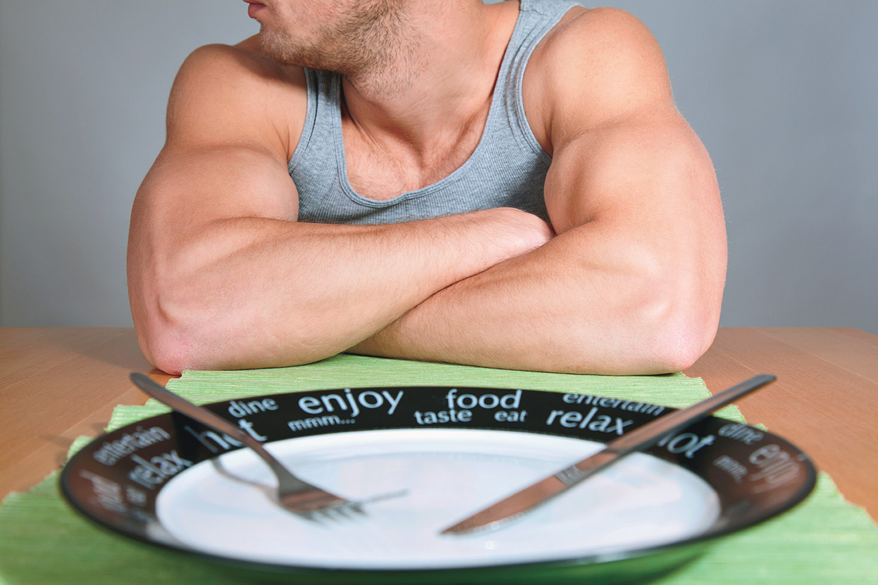 Muscular man with empty plate