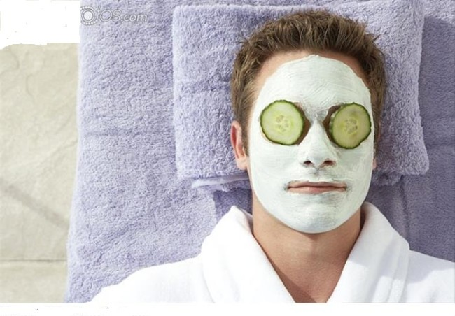 Man in a facial mask with cucumber slices over his eyes