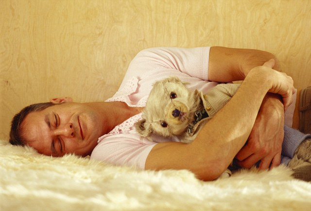 Smiling Man Sleeping with Teddy Bear in His Arms