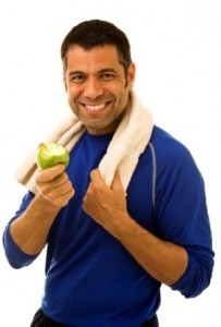 A mid adult man eating an apple after working out.