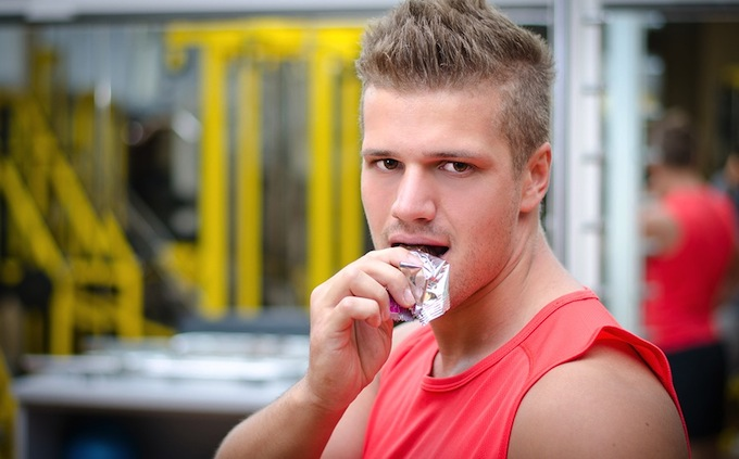 Young Man In Gym Eating Cereal Bar