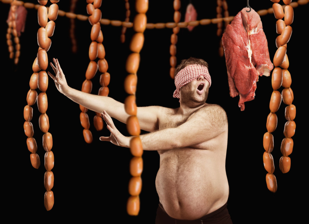 43236452 - fat man blindfolded looking for sausages over black background