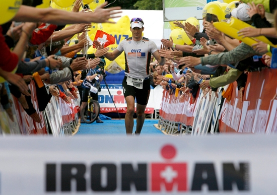 Spectators greet Ronnie Schildknecht before he crosses the finish line during the marathon leg of the Ironman Switzerland Triathlon in Zurich