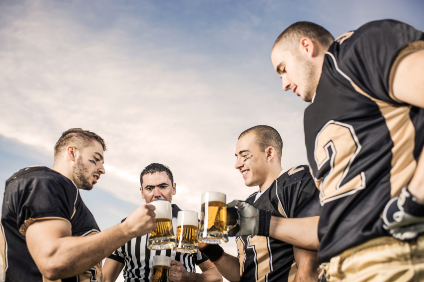 American football players celebrating victory with beer.